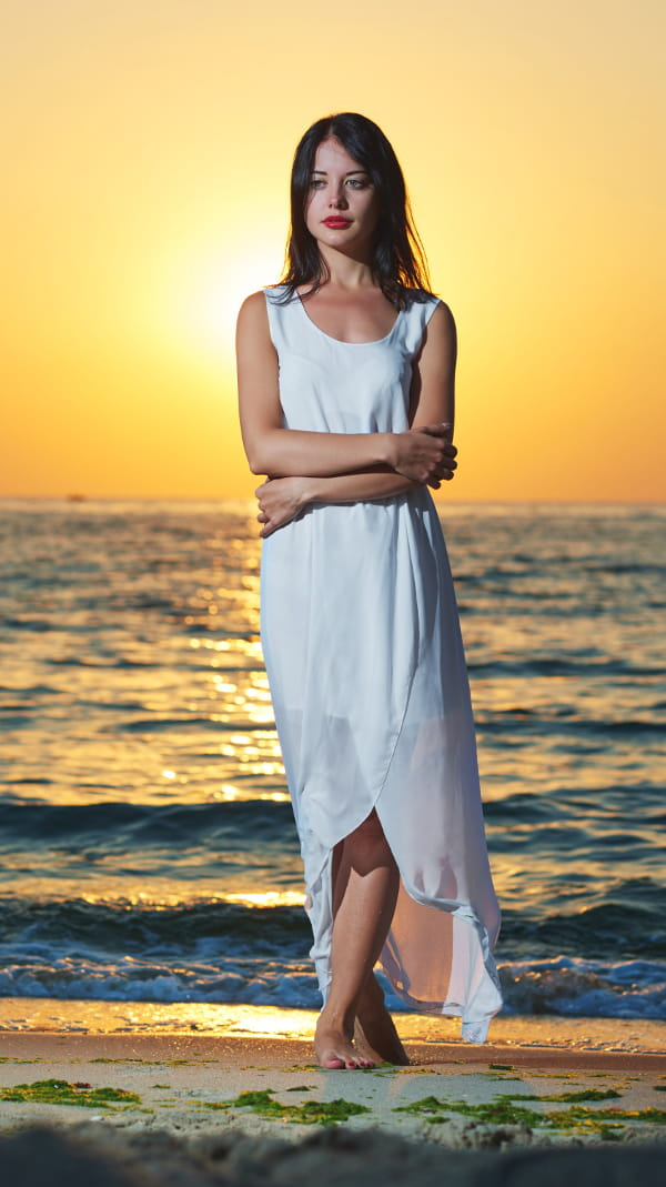 Vestido longo branco para ano novo: modelo na praia assistindo o nascer do sol.