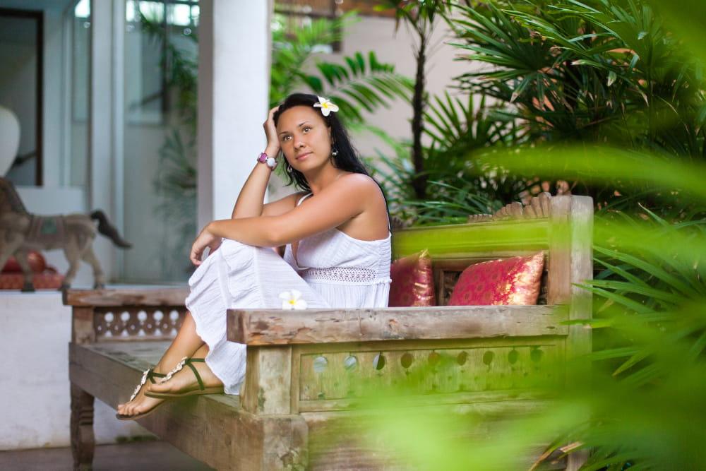 Modelo com um vestido branco longo bordado descansando no sofá de jardim.