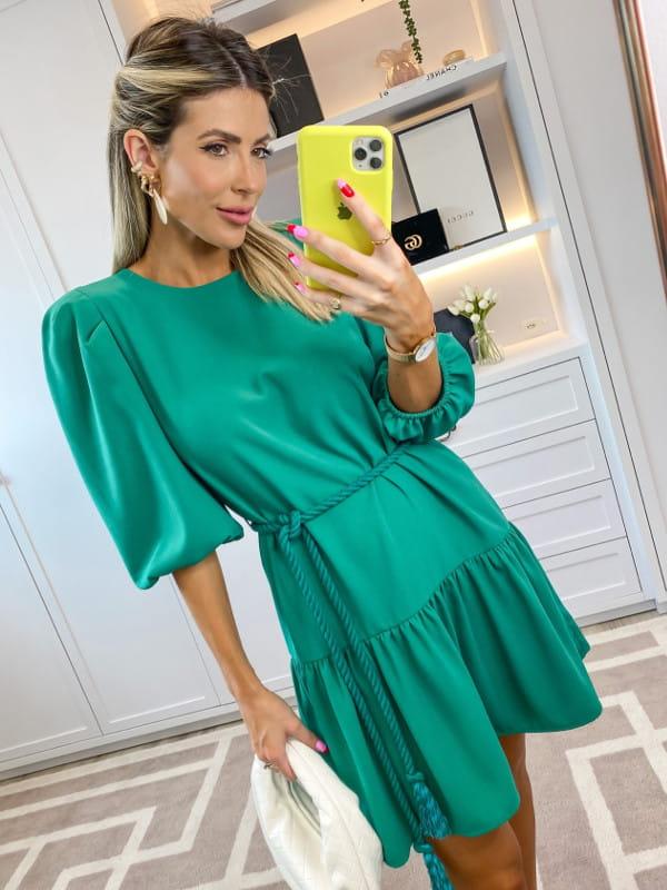 Vestidos para o Natal: modelo com um vestido verde com cinto estilo cordão.